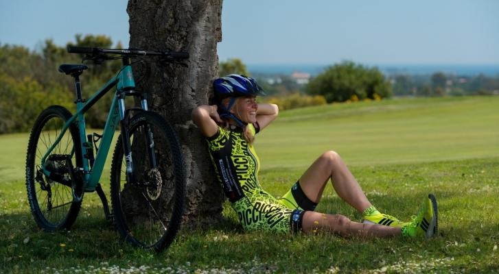 Donna riposa con bici sotto un albero